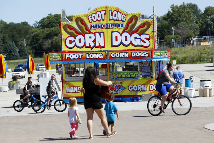 FILE - In thisJuly 28, 2020, file photo, Iowa state fairgrounds visitors pass a corn dog stand set up for the Taste of the Fair to be held this weekend in Des Moines, Iowa.  Families trying to get in a last-minute vacation before school starts better do some homework on COVID-19 restrictions before loading up the minivan. (AP Photo/Charlie Neibergall, File)