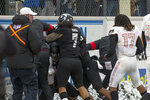FILE - In this Nov. 30, 2019, file photo, players converge during a post-game scuffle at the end of an NCAA college football game between UNLV and Nevada in Reno, Nev. The Las Vegas Raiders were the first team to play inside Allegiant Stadium. But the UNLV Rebels will be the first team to play with fans inside the $2 billion dollar venue, when they host in-state rival Nevada on Saturday, Oct. 31, 2020. (AP Photo/Tom R. Smedes, File)