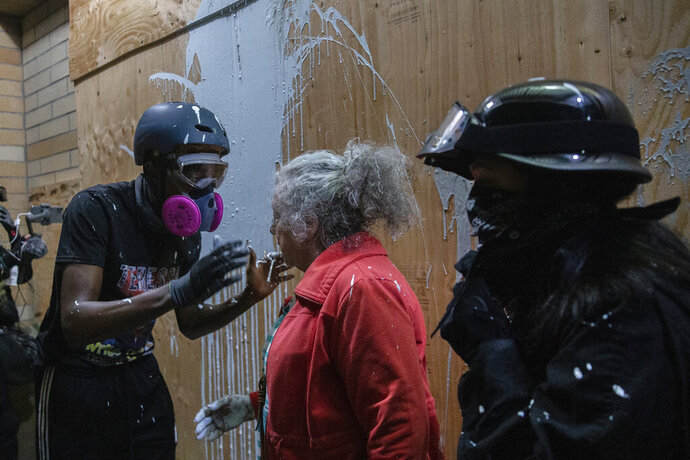A woman who lives in a Portland neighborhood targeted by protesters argues with a few black-clad demonstrators after being splashed with white paint in front of a Portland Police Bureau precinct that was being vandalized, late Thursday, Aug. 6, 2020. The woman was trying to stop the protesters from vandalizing the building when she was hit with the paint.(Mark Graves /The Oregonian via AP)