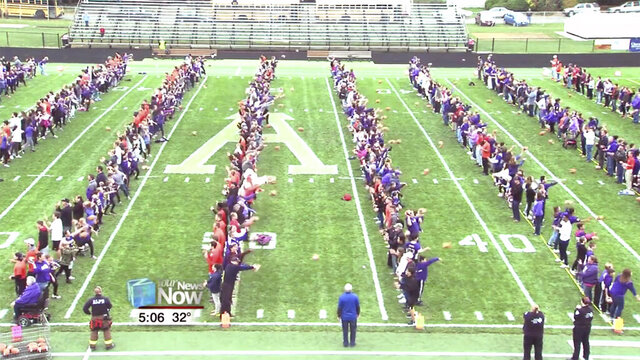 This still image taken from video provided by WLIO-TV shows 950 people throwing footballs at the same time on Oct. 25, 2019 at the Ada War Memorial Stadium football field in Ada, Ohio. The Ohio town long associated with the manufacturing of footballs has set a Guinness World Record for the most footballs thrown at once. The record-keeping organization certified the record.  (