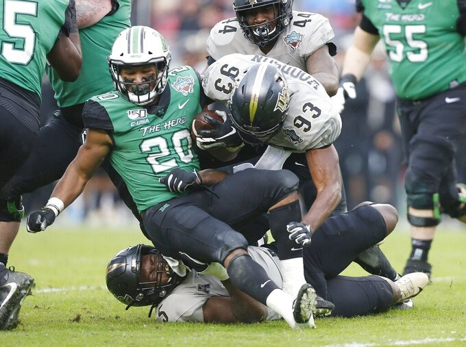 Marshall running back Brenden Knox (20) is tacked by Central Florida defensive lineman Brendon Hayes (6) after a short gain during the Gasparilla Bowl NCAA college football game Monday, Dec. 23, 2019, in Tampa, Fla. (Octavio Jones/Tampa Bay Times via AP)