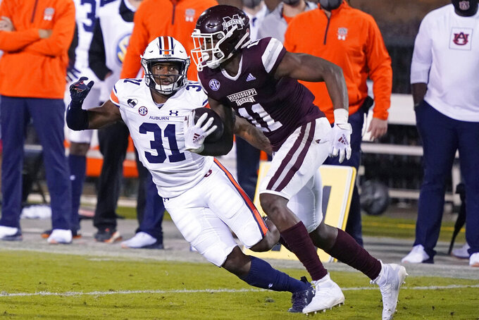 Mississippi State wide receiver Geor'quarius Spivey (11) runs upfield after catching a pass in front of Auburn defensive back Zion Puckett (31) during the second half of an NCAA college football game Saturday, Dec. 12, 2020, in Starkville, Miss. Auburn won 24-10. (AP Photo/Rogelio V. Solis)