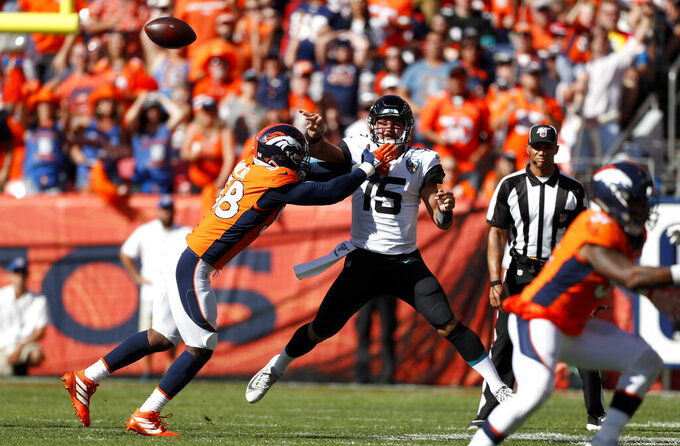 Jacksonville Jaguars quarterback Gardner Minshew (15) throws a pass under pressure from Denver Broncos outside linebacker Von Miller, left, during the first half of an NFL football game Sunday, Sept. 29, 2019, in Denver. (AP Photo/David Zalubowski)