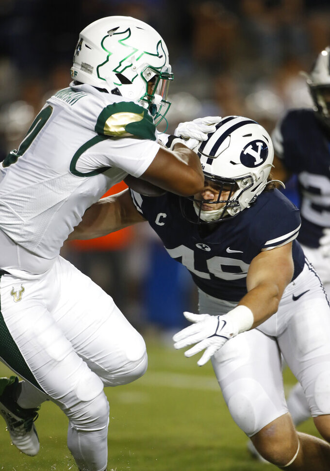 South Florida running back Jaren Mangham (0) tries to run out of the tackle by BYU linebacker Payton Wilgar (49) in the first half of an NCAA college football game Saturday, Sept. 25, 2021, in Provo, Utah. (AP Photo/George Frey)
