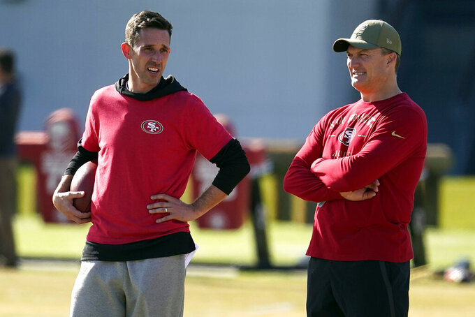 FILE- In this Jan. 24, 2020, file photo, San Francisco 49ers general manager John Lynch, right, and head coach Kyle Shanahan, left, watch as players practice at the team's NFL football training facility in Santa Clara, Calif. The San Francisco 49ers have agreed on a one-year contract with free agent tight end Jordan Reed,  Lynch announced Monday, Aug. 3, 2020. (AP Photo/Tony Avelar, File)