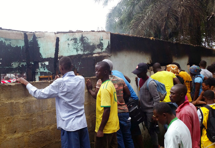 Local people turn out to view the scene of an overnight fire in Paynesville, 7 miles north east of Monrovia, Wednesday, Sept. 18, 2019. Police in Liberia say a fire at a Quranic school outside the capital, Monrovia, has killed more than 20 people and many are thought to be children. A police spokesman says the fire around midnight gutted a dormitory and school building where students slept. (AP Photo/Jonathan Paye-Layleh)