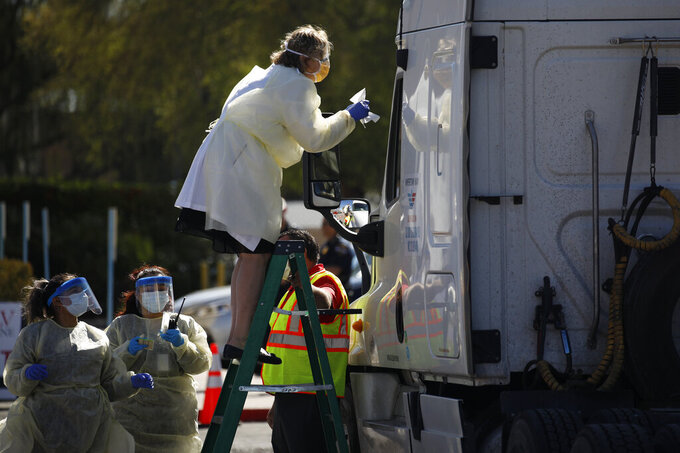 Dr. Elissa Palmer stands on a ladder to test a patient in a truck for the coronavirus at a drive thru testing site Tuesday, March 24, 2020, in Las Vegas. UNLV Medicine, the clinical arm of the UNLV School of Medicine, started conducting COVID-19 testing by appointment for people who meet the Centers for Disease Control and Prevention guidelines. (AP Photo/John Locher)