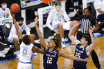 North Carolina guard Anthony Harris (0) takes a shot over Notre Dame guard Tony Sanders Jr. (12) and forward Matt Zona (25) during the second half of an NCAA college basketball game in the second round of the Atlantic Coast Conference tournament in Greensboro, N.C., Wednesday, March 10, 2021. (AP Photo/Gerry Broome)