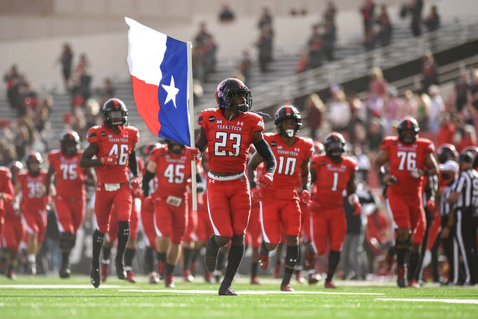 Texas Tech defensive back DaMarcus Fields (23) carries the Texas flag onto the field before the team's NCAA college football game against Baylor in Lubbock, Texas, Saturday, Nov. 14, 2020. (AP Photo/Justin Rex)