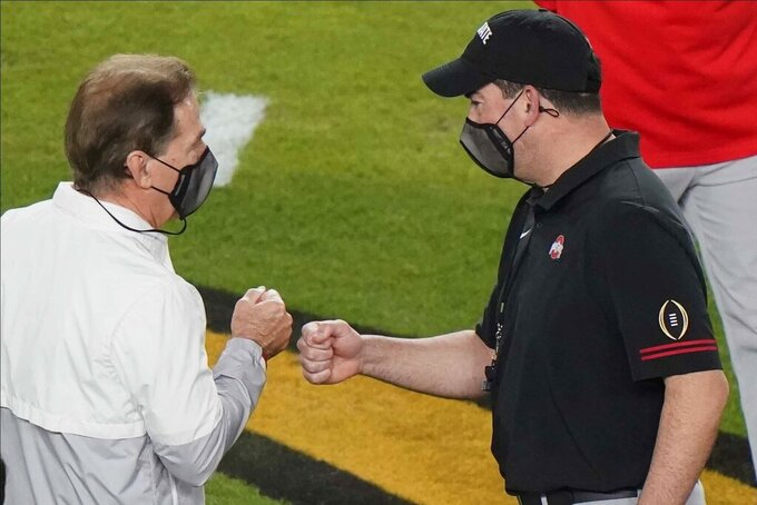 Alabama head coach Nick Saban, left, and Ohio State head coach Ryan Day, meet on the field before an NCAA College Football Playoff national championship game, Monday, Jan. 11, 2021, in Miami Gardens, Fla. (AP Photo/Wilfredo Lee)