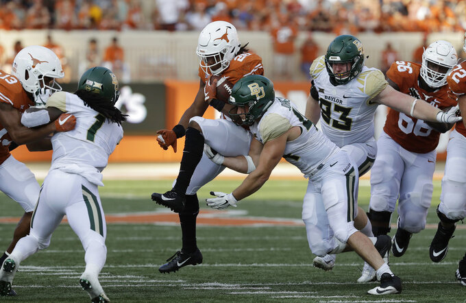 Texas running back Keaontay Ingram (26) is hit by Baylor linebacker Clay Johnston (44) during the second half of an NCAA college football game, Saturday, Oct. 13, 2018, in Austin, Texas. (AP Photo/Eric Gay)