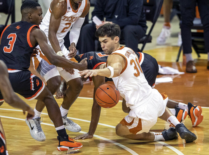 Texas forward Brock Cunningham (30) battles for the loose ball against Sam Houston State guard Demarkus Lampley (3) during the first half of an NCAA college basketball game, Wednesday, Dec. 16, 2020 in Austin, Texas. (Ricardo B. Brazziell/Austin American-Statesman via AP)
