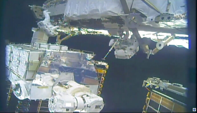 In this image take from NASA video, astronauts Jessica Meir, right, and Christina Koch install batteries for the International Space Station's solar power grid during a space walk Monday, Jan. 20, 2020. (NASA via AP)