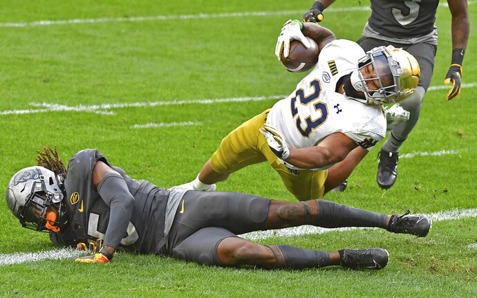 Notre Dame running back Kyren Williams dives into the end zone for a touchdown against Pitt defensive back Jason Pinnock in the second quarter of an NCAA college football game, Saturday, Oct. 24, 2020, in Pittsburgh. (Matt Freed/Pittsburgh Post-Gazette via AP)