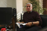 In this Oct. 29, 2019, photo, Ebrahim Asgharzadeh, one of the Iranian student leaders of the 1979 U.S. Embassy takeover, speaks in an interview with The Associated Press as he holds a book about the takeover, in Tehran, Iran. Asgharzadeh says he now regrets the seizure of the diplomatic compound and the 444-day hostage crisis that followed. (AP Photo/Vahid Salemi)
