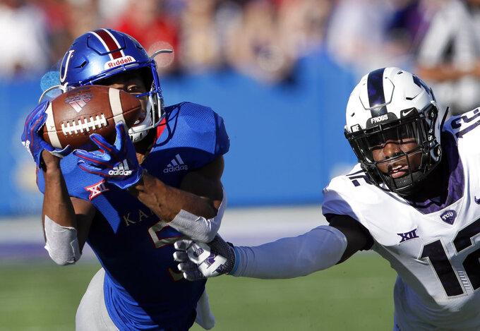 Kansas wide receiver Stephon Robinson (5) catches a pass while covered by TCU cornerback Jeff Gladney (12) during the second half of an NCAA college football game in Lawrence, Kan., Saturday, Oct. 27, 2018. (AP Photo/Orlin Wagner)