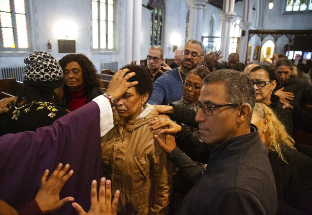 In this Sunday, Dec. 15, 2019, photo, the Rev. Luis Barrios, left, places his hand on the head of Mercedes Katrocino, center, a deaf congregant, as he and the rest of the congregation pray for Katrocino's health and failing eyesight at Holyrood Episcopal Church in New York on Sunday, Dec. 15, 2019. (AP Photo/Jessie Wardarski)