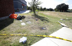 A parachute and other items remain outside an Ole Donut where one pilot landed after ejecting from a military training jet before it crashed Sunday, Sept. 19, 2021, in Lake Worth, Texas. The jet crashed Sunday in a neighborhood near Fort Worth, Texas, injuring the two pilots and damaging three homes but not seriously hurting anyone on the ground, authorities said.  (Amanda McCoy/Star-Telegram via AP)