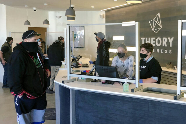 Buyers line up to purchase cannabis products at Theory Wellness on Friday, Oct. 9, 2020, in South Portland, Maine. Friday is the first day of legal marijuana sales for adult recreational use in the state. (AP Photo/David Sharp)