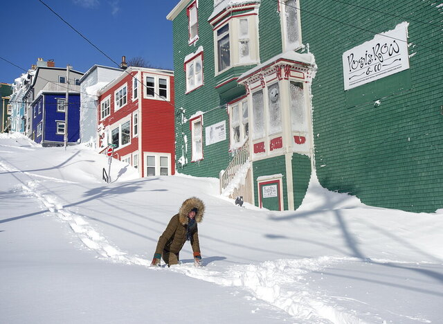 A residents makes their way through the snow in St. John's, Newfoundland on Saturday, Jan. 18, 2020. The state of emergency ordered by the City of St. John's is still in place, leaving businesses closed and vehicles off the roads in the aftermath of the major winter storm that hit the Newfoundland and Labrador capital.  (Andrew Vaughan/The Canadian Press via AP)