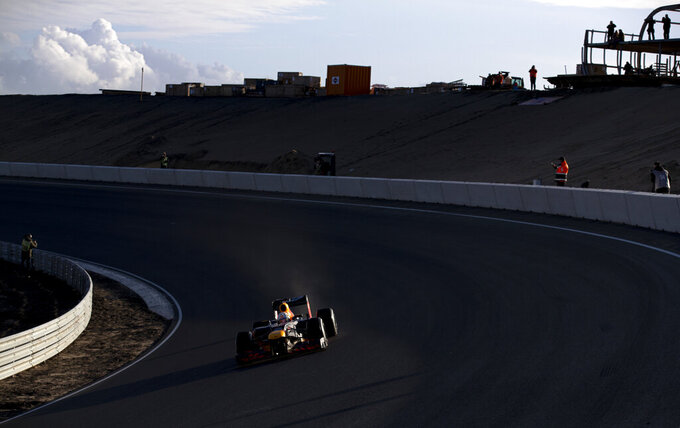 F1 driver Max Verstappen of The Netherlands drives his car through the Arie Luyendyk corner, one of the two banked corners, during a test and official presentation of the renovated F1 track in the beachside resort of Zandvoort, western Netherlands, Wednesday, March 4, 2020. (AP Photo/Peter Dejong)