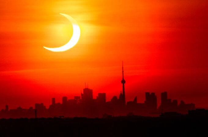 An annular solar eclipse rises over the skyline of Toronto on Thursday, June 10, 2021.  (Frank Gunn/The Canadian Press via AP)