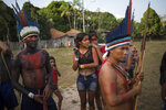 In this Sept. 3, 2019 photo, people gather for a meeting of the Tembe tribes in the Tekohaw village, in Para state, Brazil. Under a thatch-roof shelter in the Amazon rainforest, warriors wielding bows and arrows, elderly chieftains in face paint and nursing mothers gathered to debate a plan that some hope will hold at bay the loggers and other invaders threatening the tribes of the Tembe. (AP Photo/Rodrigo Abd)