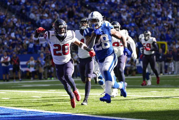 Indianapolis Colts' Jonathan Taylor (28) runs past Houston Texans' Justin Reid (20) for a touchdown during the second half of an NFL football game, Sunday, Oct. 17, 2021, in Indianapolis. (AP Photo/AJ Mast)