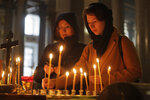 Women light candles in memory of victims of shooting in the vocational college in Kerch, Crimea, in a church in St.Petersburg, Russia, Thursday, Oct. 18, 2018.  An 18-year-old student strode into his vocational school in Crimea, Wednesday, then pulled out a shotgun and opened fire, killing 19 students and wounding more than 50 others before killing himself. (AP Photo/Dmitri Lovetsky)