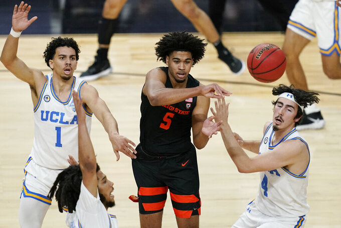 Oregon State's Ethan Thompson (5) passes around UCLA's Jules Bernard (1) and Jaime Jaquez Jr. (4) during the first half of an NCAA college basketball game in the quarterfinal round of the Pac-12 men's tournament Thursday, March 11, 2021, in Las Vegas. (AP Photo/John Locher)