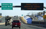 An electronic road sign warns motorists on eastbound Sixth Avenue of the spiraling increase in coronavirus cases and the heightened alert in place for residents early Monday, Nov. 30, 2020, in Lakewood, Colo. (AP Photo/David Zalubowski)