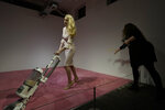 A spectator tosses crumbs for an Ivanka Trump lookalike to vacuum at Jennifer Rubell's art exhibit