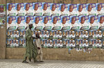 A child leads a blind man as they walk past a wall of campaign posters in Kano, in northern Nigeria, Saturday, Feb. 16, 2019. A civic group monitoring Nigeria's now-delayed election says the last-minute decision to postpone the vote a week until Feb. 23
