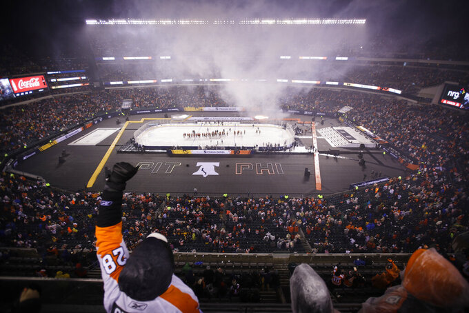 Philadelphia Flyers fans celebrate after Claude Giroux scored against the Pittsburgh Penguins during overtime of an NHL Stadium Series hockey game at Lincoln Financial Field, Saturday, Feb. 23, 2019, in Philadelphia. Philadelphia won 4-3. (AP Photo/Matt Rourke)