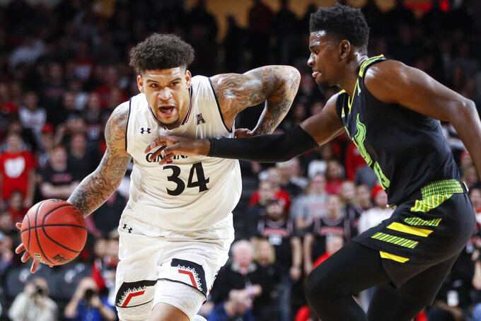 Cincinnati's Jarron Cumberland (34) drives against South Florida's Justin Brown (13) in the first half of an NCAA college basketball game, Tuesday, Jan. 15, 2019, in Cincinnati. (AP Photo/John Minchillo)