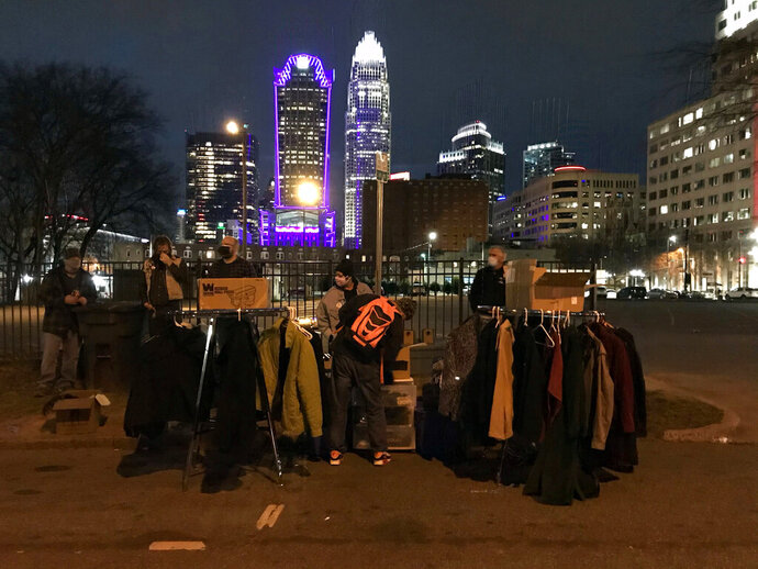 In this Jan. 24, 2021, photo, provided by Magena Morris, volunteers help residents of Tent City, Charlotte, North Carolina's largest homeless encampment, shop for clothing and other goods at the Mutual Aid Free Store set up by local aid groups Bleach Impaired and Not Fade Away. Morris, the cofounder of Bleach Impaired who was once homeless herself, started the initiative after noticing an increase in homelessness the previous year. (Magena Morris via AP)