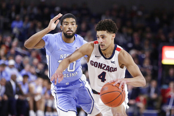 Gonzaga guard Ryan Woolridge, right, drives against North Carolina guard K.J. Smith during the second half of an NCAA college basketball game in Spokane, Wash., Wednesday, Dec. 18, 2019. Gonzaga won 94-81. (AP Photo/Young Kwak)