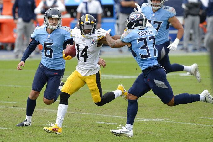 Pittsburgh Steelers' Ray-Ray McCloud (14) runs between Tennessee Titans punter Brett Kern (6) and Amani Hooker (37) as McCloud returns a punt 57 yards in the first half of an NFL football game Sunday, Oct. 25, 2020, in Nashville, Tenn. (AP Photo/Mark Zaleski)