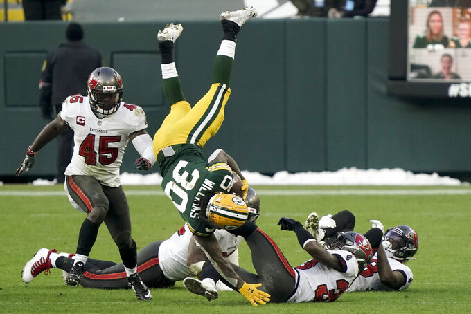 Green Bay Packers' Jamaal Williams (30) is upended by the Tampa Bay Buccaneers during the second half of the NFC championship NFL football game in Green Bay, Wis., Sunday, Jan. 24, 2021. (AP Photo/Morry Gash)