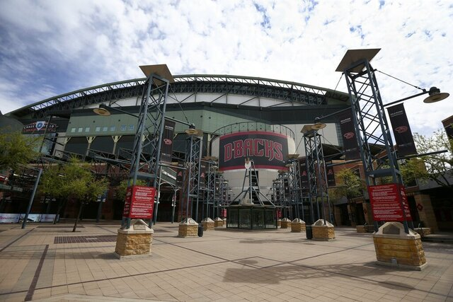 FILE - In this Thursday, March 26, 2020 file photo, The main entrance in front of Chase Field is devoid of activity in Phoenix. Putting all 30 teams in the Phoenix area this season and playing in empty ballparks was among the ideas discussed Monday, April 6, 2020 during a call among five top officials from MLB and the players' association that was led by Commissioner Rob Manfred, people familiar with the discussion told The Associated Press.  (AP Photo/Ross D. Franklin, File)