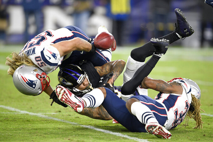 Baltimore Ravens' Chris Moore, center, fumbles a kickoff return as New England Patriots defensive end Chase Winovich (50) and running back Brandon Bolden make the hit during the second half of an NFL football game, Sunday, Nov. 3, 2019, in Baltimore. The Ravens recovered the fumble. (AP Photo/Nick Wass)