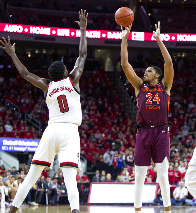 Virginia Tech's Kerry Blackshear Jr. (24) shoots over North Carolina State's DJ Funderburk (0) during the second half of an NCAA college basketball game in Raleigh, N.C., Saturday, Feb. 2, 2019. (AP Photo/Ben McKeown)