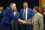 Chicago Mayor-elect Lori Lightfoot, right, shakes hands with former mayoral candidate Cook County Board President Toni Preckwinkle as Rev. Jesse Jackson look on during a press conference at the Rainbow PUSH organization, Wednesday morning, April 3, 2019, in Chicago. (Ashlee Rezin/Chicago Sun-Times via AP)