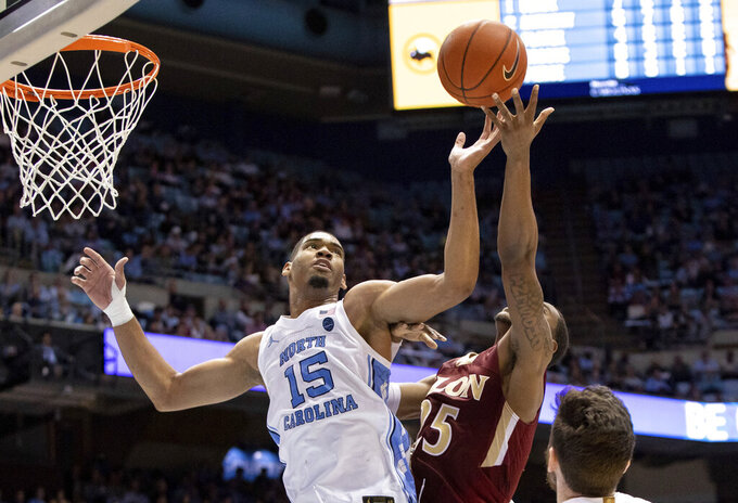 North Carolina's Garrison Brooks (15) and Elon's Hunter Woods (25) battle for a rebound during the second half of an NCAA college basketball game in Chapel Hill, N.C., Wednesday, Nov. 20, 2019. (AP Photo/Ben McKeown)
