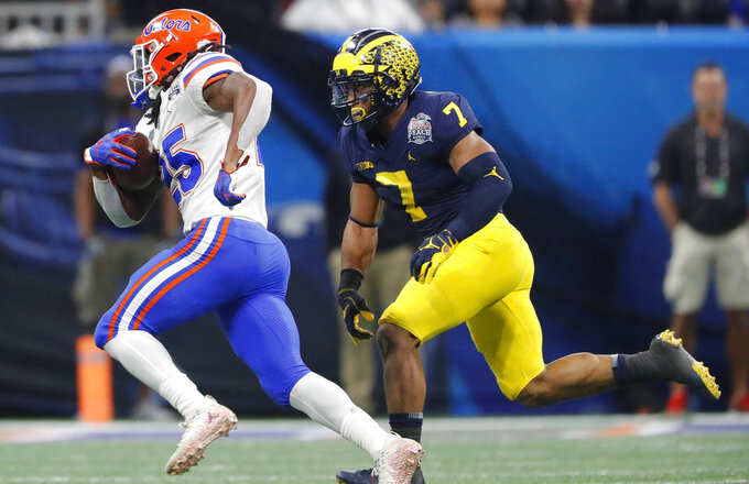 Florida running back Jordan Scarlett (25) runs against Michigan linebacker Khaleke Hudson (7) during the first half of the Peach Bowl NCAA college football game, Saturday, Dec. 29, 2018, in Atlanta. (AP Photo/John Bazemore)