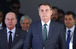 Brazil's President Jair Bolsonaro, right, and his Defense Minister Fernando Azevedo leave after meeting with military commanders at the Defense Ministry in Brasilia, Brazil, Tuesday, Jan. 7, 2020. Bolsonaro spoke about maintaining commercial ties with Iran this morning, said he would speak to his foreign minister about talks with Iran, and reiterated that Brazil opposes terrorism. (AP Photo/Eraldo Peres)