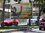 In this Tuesday, July 2, 2019 photo, motorists pass by a Popular Mobilization poster in Baghdad, Iraq. The Iraqi government's move to place Iranian-backed militias under the command of the armed forces is a political gamble by a prime minister increasingly caught in the middle of a dangerous rivalry between Iran and the U.S., the two main power brokers in Iraq.  (AP Photo/Hadi Mizban)