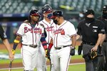 Atlanta Braves' Ronald Acuna Jr., left, is walked to first base after he was hit by a pitch during the third inning in Game 1 of a baseball National League Division Series against the Miami Marlins Tuesday, Oct. 6, 2020, in Houston. (AP Photo/Eric Gay)