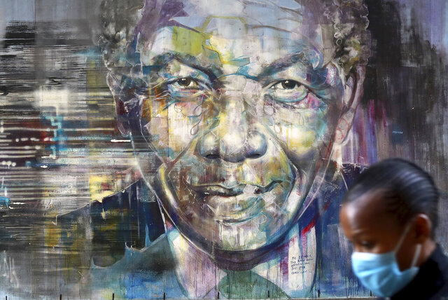 A woman wearing a face mask walks past a mural of former President Nelson Mandela in Cape Town, South Africa, Saturday July 18, 2020, as the country celebrates International Mandela Day. Mandela's fight for freedom and human rights makes him the most influential person among Africa's youth, according to a survey conducted across the continent. (AP Photo/Nardus Engelbrecht)