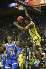 Oregon's Shakur Juiston, right, dunks the ball over UCLA's David Singleton during the first half of an NCAA college basketball game in Eugene, Ore., Sunday, Jan. 26, 2020. (AP Photo/Chris Pietsch)